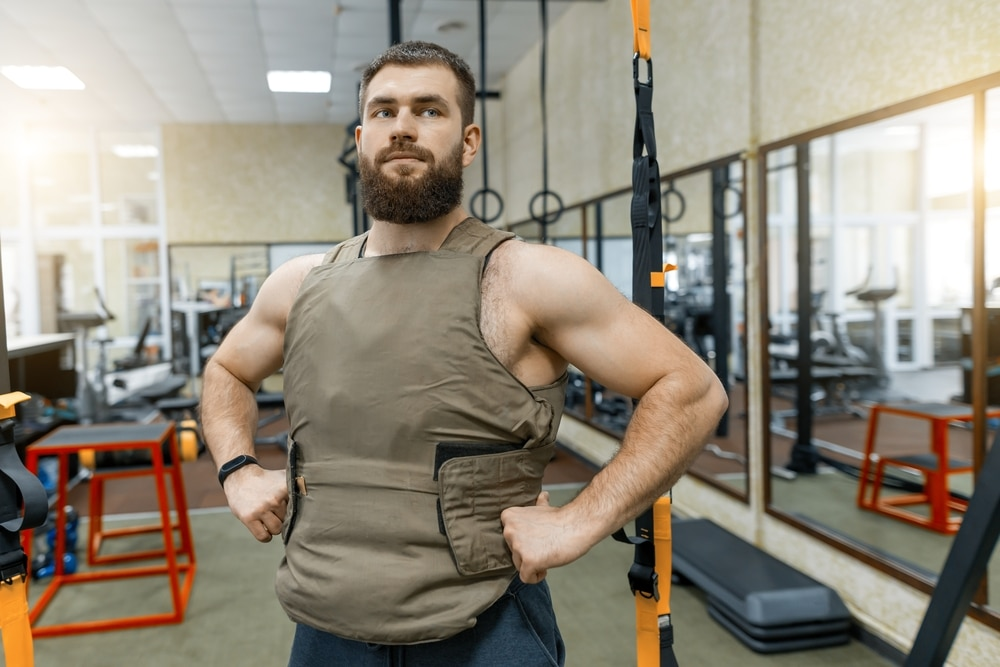 A muscular man gets ready for a workout by wearing a full upper body jacket.